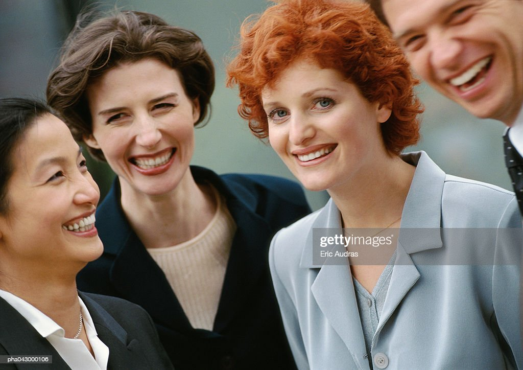 Group of four business people, smiling : Stockfoto