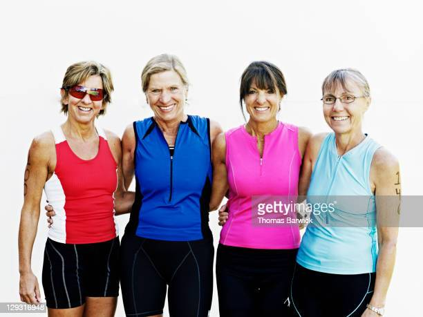 Group of four female triathletes standing smiling