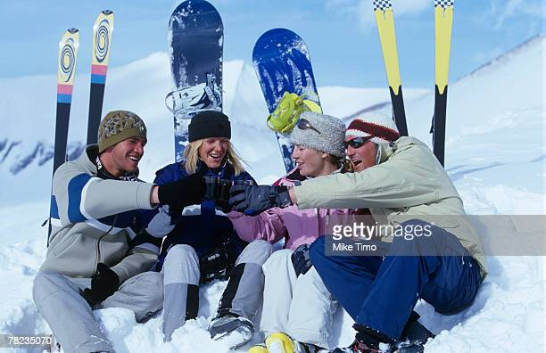 group of four friends sitting in snow talking and drinking mulled wine