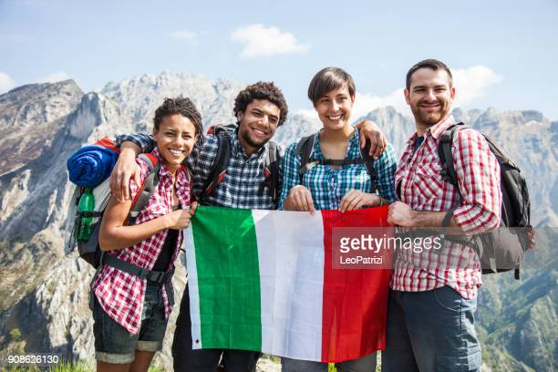 Group of four friends spending a day hiking in mountain in a beautiful spring sunny day