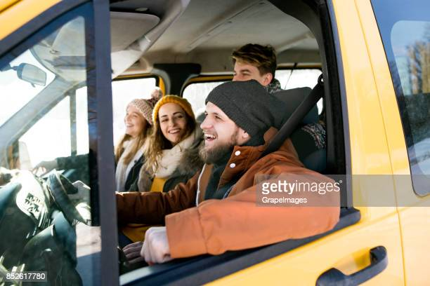 Group of four friends travelling by car.