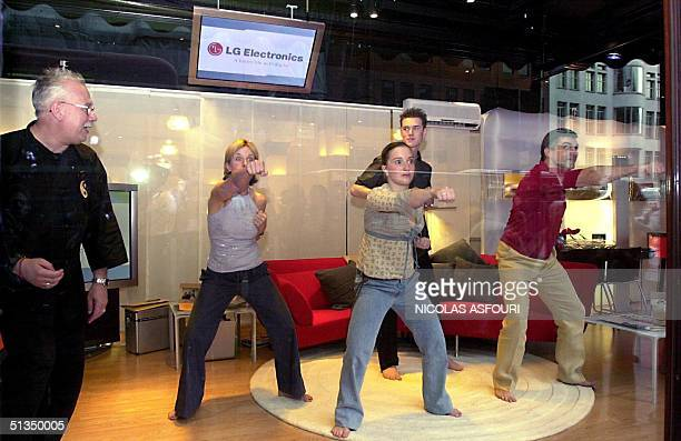 A group of four from left Sarah Wooster Steve Wilson Charlie Parker and Carl Newman practice 20 May 2002 feng shiu with a teacher in a Harrods store...