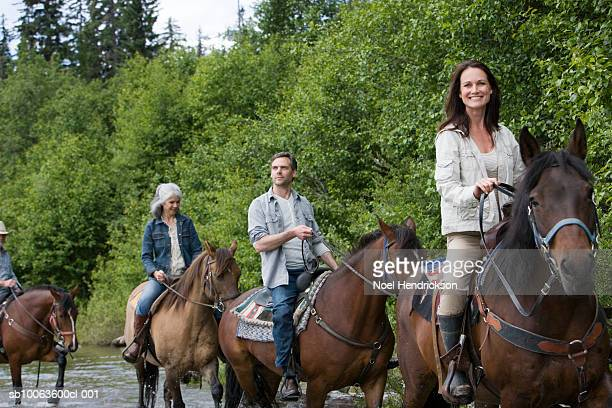 group of four horse riders crossing river, woman looking at camera - andare a cavallo foto e immagini stock