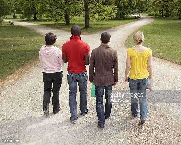 Group of four multi-ethnic students walking on forked footpath