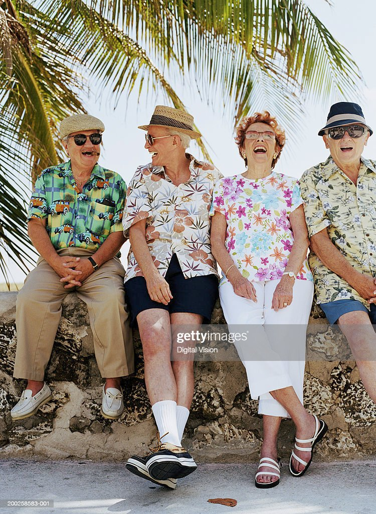 Group of four senior people sitting on wall outdoors, laughing : Stock Photo