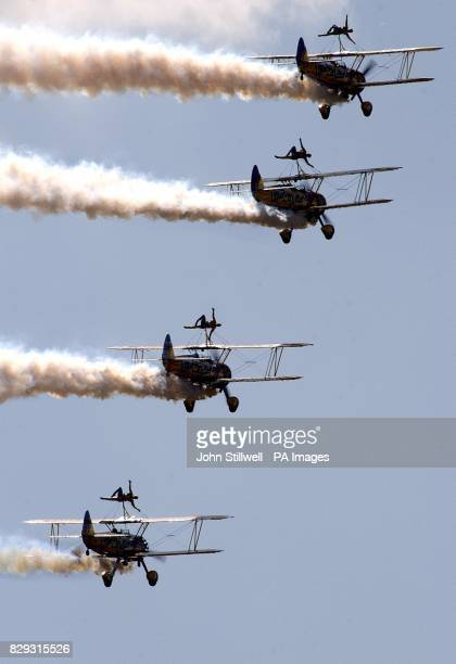 A group of four wingwalkers from the 'utterley butterly' display team take up their positions on top of their Stearman biplanes during an airshow at...
