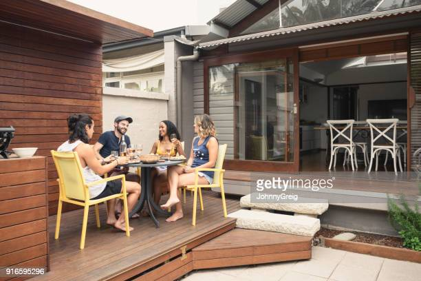 group of four young adults relaxing on patio outside house with food and drink - patio stock pictures, royalty-free photos & images