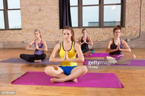 Groep van vier jonge vrouwen in het centrum van de gezondheid van de oefening van het Yoga Studio