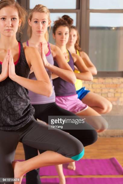 Gruppe von vier jungen Frauen im Studio Yoga-Übung-Gesundheits-Zentrum