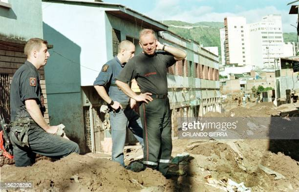 A group of french firefighters look at a street in Tegucigala Honduras that is covered with mud and sand before they began cleaning it 14 November...
