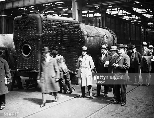 A group of French railway officials standing next to a worker riveting a locomotive boiler during a visit to the GWR works at Swindon Wiltshire 8th...