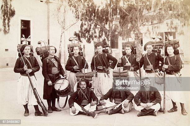 A group of French soldiers pose in a courtyard carrying their gear in Algiers