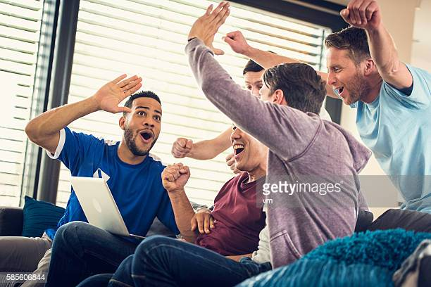 group of frends watching game on laptop - net sports equipment stock pictures, royalty-free photos & images