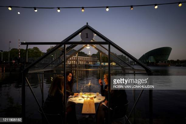 TOPSHOT A group of friend have dinner in a socalled quarantine greenhouses in Amsterdam on May 5 2020 as the country fights against the spread of the...