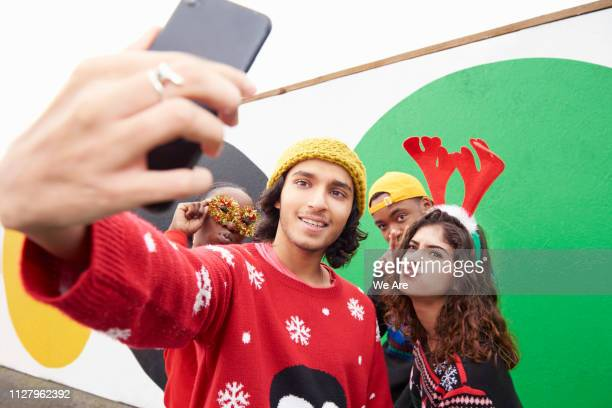 group of friend in christmas jumpers taking a selfie - antler stock pictures, royalty-free photos & images