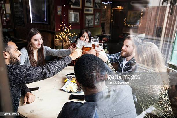 Group of friend toasting at a pub