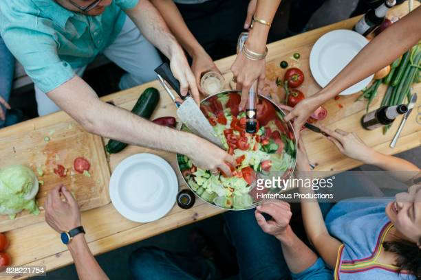 Group Of Friends All Helping Prepare Food For Barbecue Together