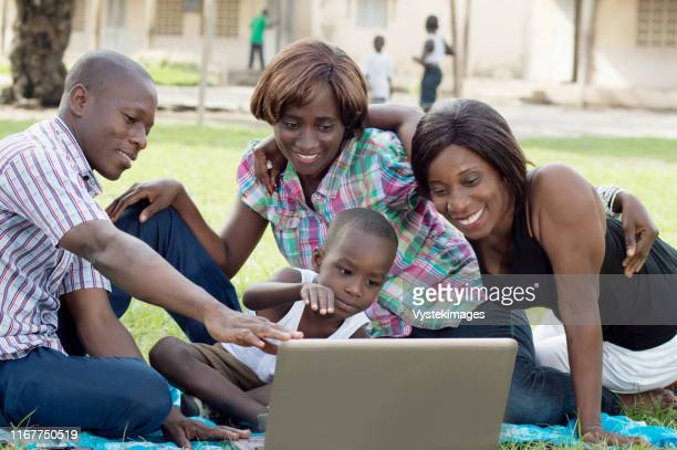 a group of friends and a child looking at a laptop screen . they are all happy. - femme ivoirienne photos et images de collection