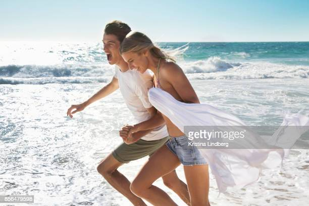 group of friends and coupple walking and hanging out on the beach, waring shorts and tops - heterosexual couple stock pictures, royalty-free photos & images