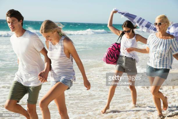 Group of friends and coupple walking and hanging out on the beach, waring shorts and tops