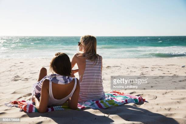 group of friends and coupple walking and hanging out on the beach, waring shorts and tops - beach stock pictures, royalty-free photos & images