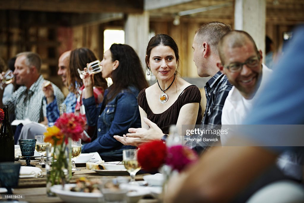 Group of friends and family dining at table : Stock Photo