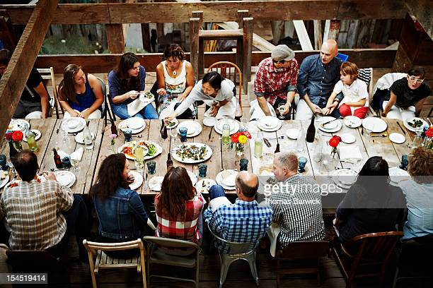 group of friends and family dining overhead view - partage photos et images de collection