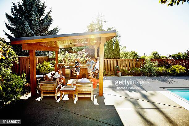 group of friends and family relaxing under cabana - gazebo foto e immagini stock