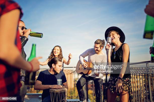 group of friends are celebrating with a concert on the roof terrace - performance group stock pictures, royalty-free photos & images