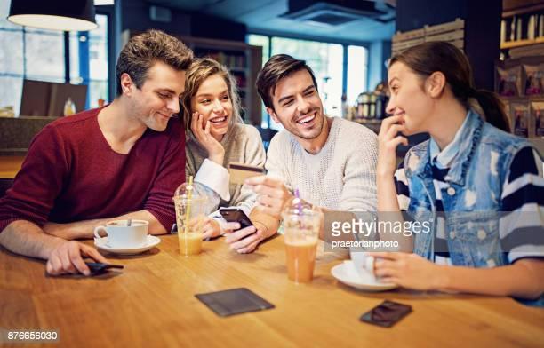 Groupe d'amis paient en ligne à l'aide de téléphone mobile et carte de crédit ensemble dans le café