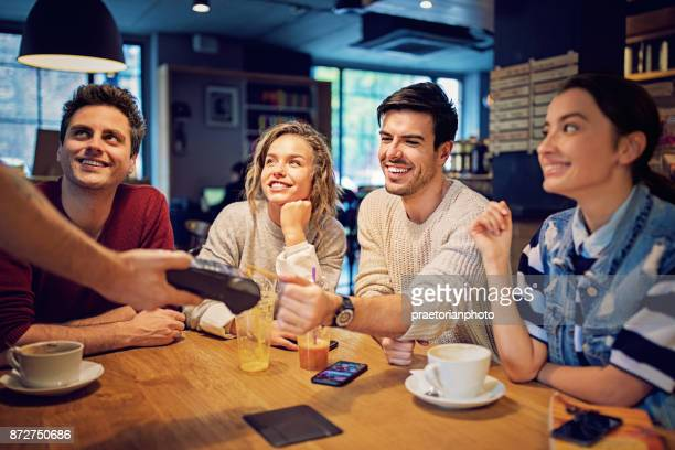 Groupe d'amis paient à l'aide de carte de crédit sans contact dans le café