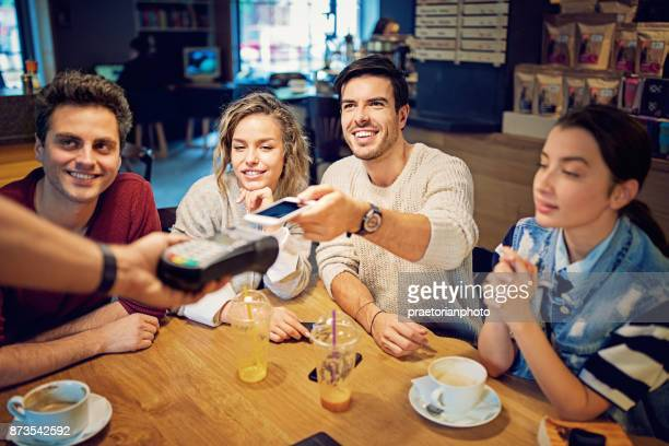 Groupe d'amis paient à l'aide de téléphone portable dans le café