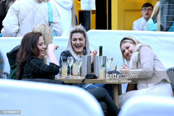 Group of friends are seen laughing while drinking in an outdoor seating venue on April 16, 2021 in Manchester, England. Pubs and Restaurants are...