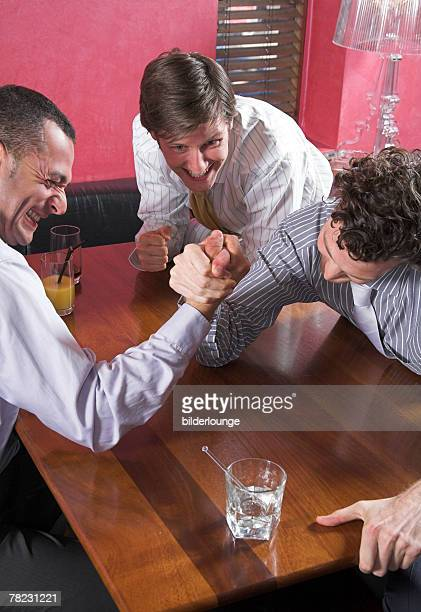 group of friends arm wrestling in bar