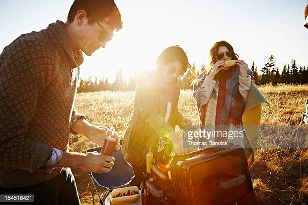 Group of friends around barbecue eating food