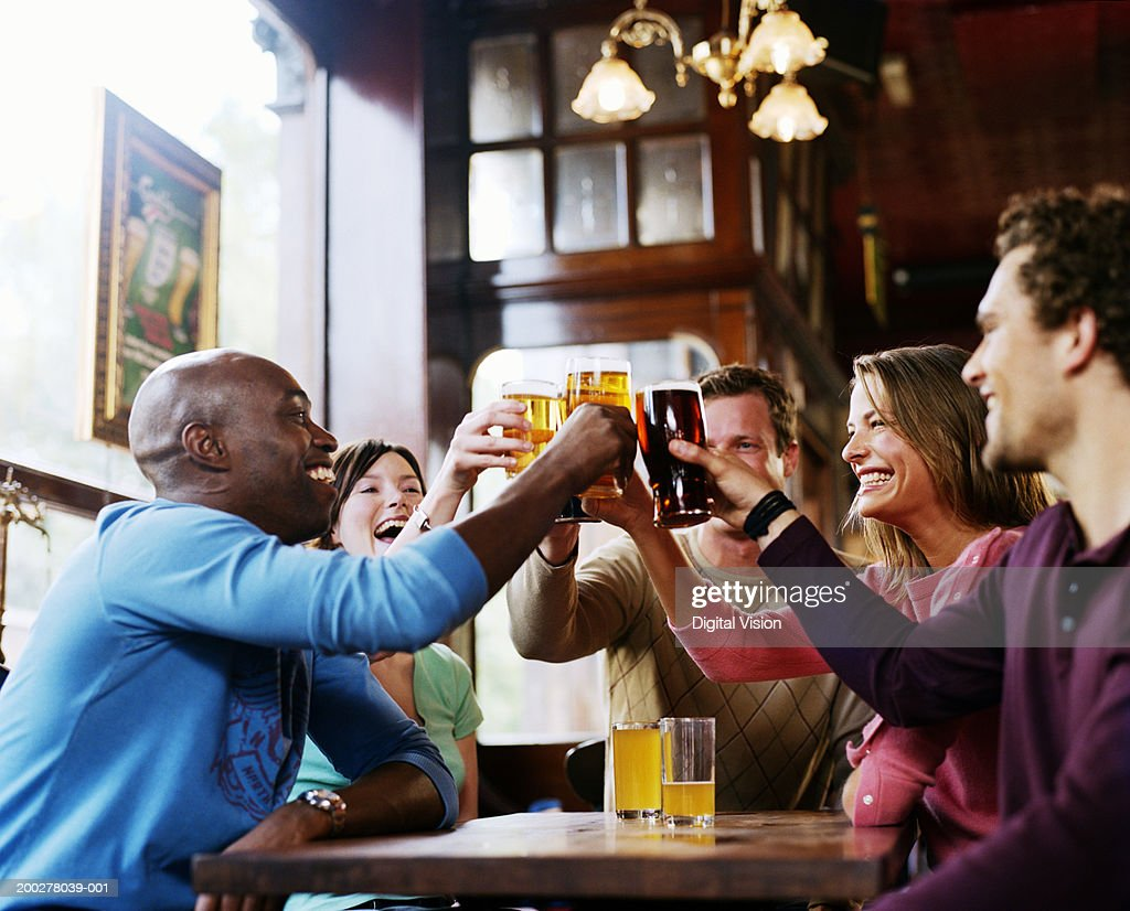 Group of friends around pub table, toasting drinks, smiling, side view : Foto de stock