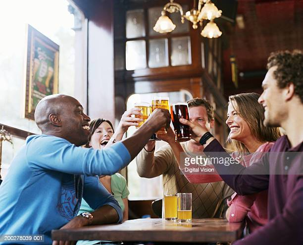 Group of friends around pub table, toasting drinks, smiling, side view