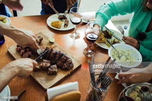 Group Of Friends Around The Dining Table While The Meat Is Being Carved This Has Been Shot from Above