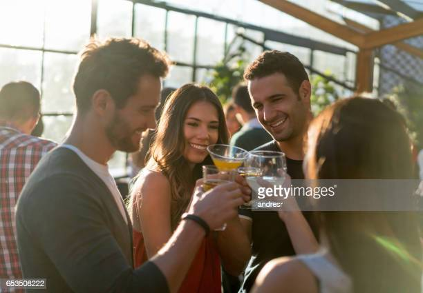 group of friends at a bar making a toast - cocktail party stock pictures, royalty-free photos & images