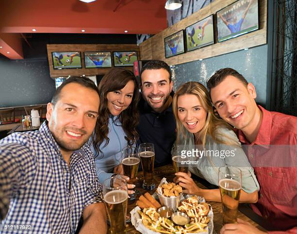 Group of friends at a bar taking a selfie