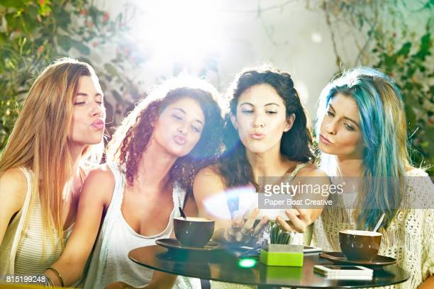 group of friends at a cafe taking a selfie and pouting with their lips - solo ragazze foto e immagini stock