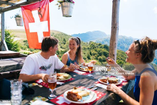 group of friends at alpine hut eating meal looking out at view - hut stock pictures, royalty-free photos & images