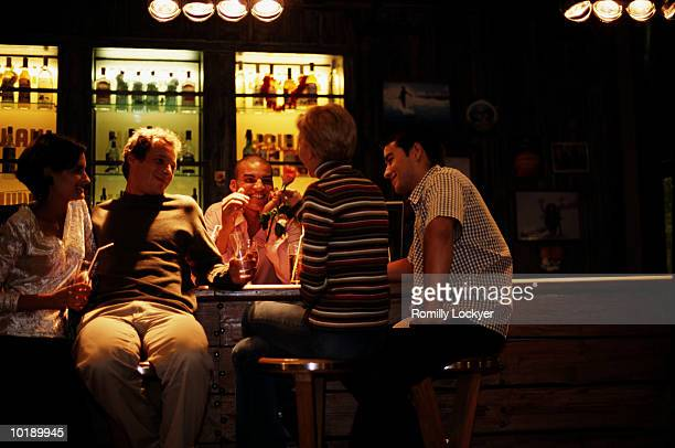 Group of friends at bar, woman holding rose