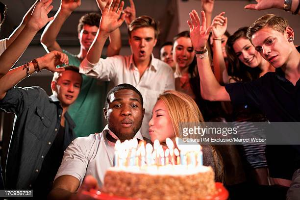Group of friends at birthday party with cake