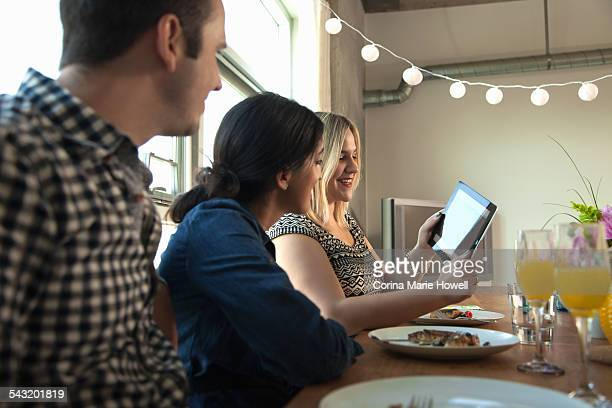 Group of friends at dinner table, looking at digital tablet screen