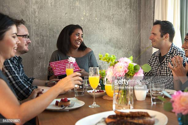 Group of friends at dinner table, Young woman holding wrapped gift