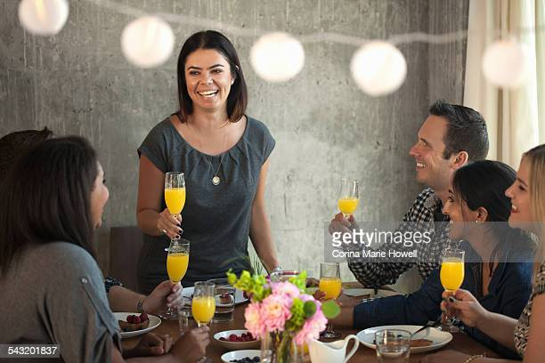 Group of friends at dinner table, young woman making toast