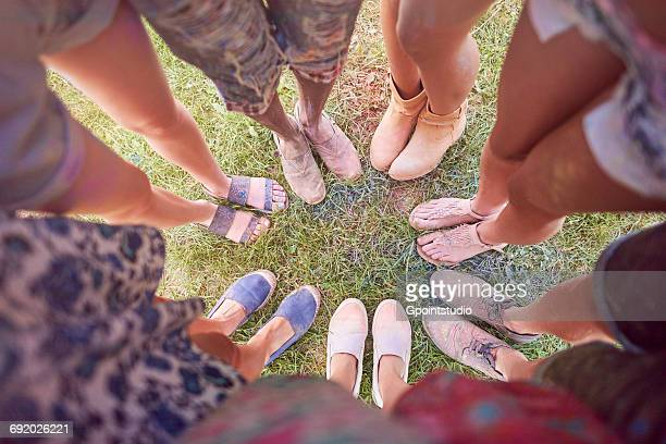 Group of friends at festival, covered in colourful powder paint, standing in circle, elevated view of feet