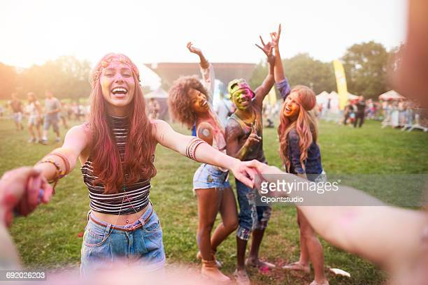 Group of friends at festival, covered in colourful powder paint