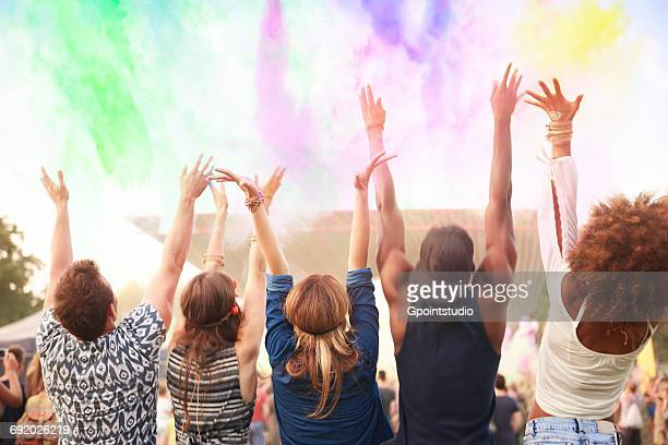 Group of friends at festival, throwing colourful powder paint in air, rear view